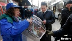 "A woman hands out free newspapers with the headline ""Crimea Chooses Russia"" on a street in Simferopol on March 17."