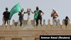 Палестинец держит флаг ХАМАС, когда он стоит рядом с другими на пешеходной улице мечети Аль-Акса после столкновений с израильской полицией в комплексе, где находится мечеть Аль-Акса, 10 мая 2021 г.