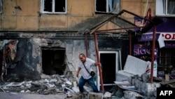 Людина залишає зруйновану внаслідок бойових дій будівлю, Донецьк, 20 серпня 2014 року