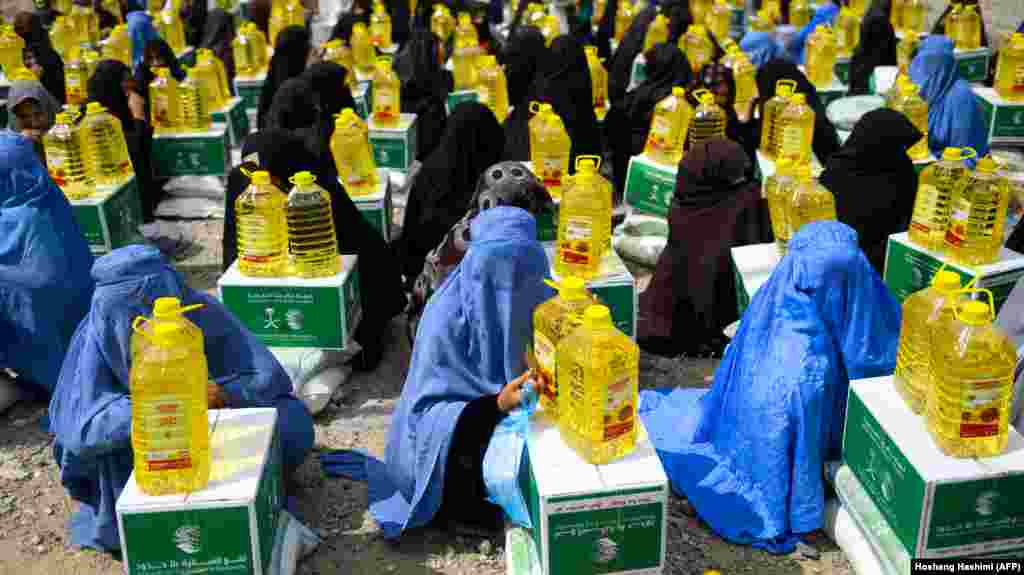 Afghan burqa-clad women sit as they receive aid items by a charity during the holy month of Ramdan in Herat Province on May 23. (AFP/Hoshang Hashimi)