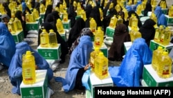 FILE: Afghan women receive food aid in the western province of Herat in May.