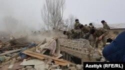 Люди в военной униформе разбирают завалы на месте крушения грузового самолета в окрестностях Бишкека. 16 января 2016 года.
