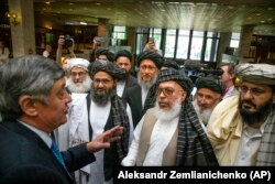 Russia's special presidential envoy for Afghan affairs, Zamir Kabulov (left), speaks to the Taliban's top political leader, Mullah Abdul Ghani Baradar (third from left), and other members of the Taliban delegation at peace talks in Moscow in May 2019.