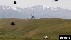 Юрта кочевников у подножия гор на фоне построенной в советское время обсерватории. Плато Ассы, август 2013 года.