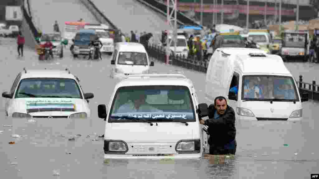 OCTOBER 25, 2012 -- A Syrian man pushes his car after it stopped in a flooded avenue following heavy rain in the northern Syrian city of Aleppo. (AFP/Philippe Desmazes)
