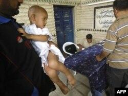 Иракский мальчик на руках у своего отца в ожидании операции по обрезанию. Багдад, 10 июля 2009 года.