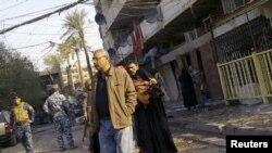د بغداد په مرکز کې له چاودنې وروسته د یوې ودانۍ اوسېدونکي په وتو دي.۲۲ ډسمبر ۲۰۱۱