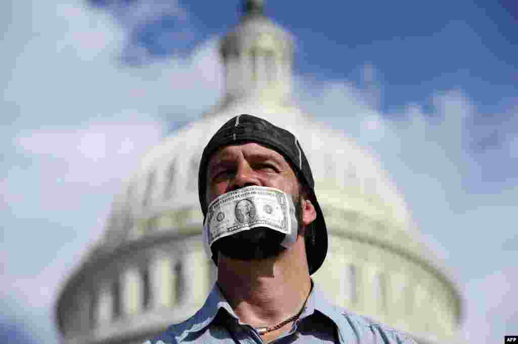 A protester covers his mouth with a dollar bill as he joins others in front of the U.S. Capitol in Washington, D.C., to urge Congress to pass a budget bill to keep the federal government from shutting down. (AFP/Jewel Samad)