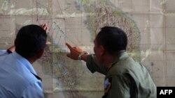 Индонезия қорғаныс министрлігінің қызметкерлері картадан Malaysia Airlines лайнерінің жолын қарап тұр.