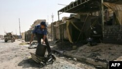 An Iraqi police officer moves debris off the main road following a double explosion in the Sadr City district of Baghdad.