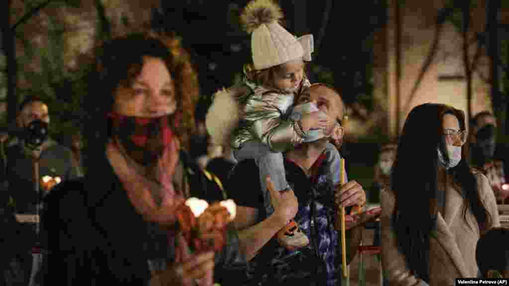 Father carries his daughter as they attend midnight Easter Orthodox Mass in front of Alexander Nevsky Cathedral in Sofia, Bulgaria, on April 19. The Bulgarian Orthodox Church resisted calls to close churches for Easter, the most significant holiday in the Orthodox calendar. But following demands by health authorities, it urged worshipers to pray at home rather than going to church.