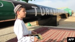 A Turkmen boy in traditional dress waits for the president at an official launch ceremony for the East-West gas trunk pipeline in Shatlyk in May 2010.