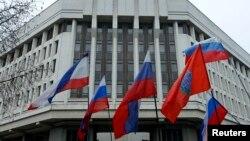 Люди тримають російські прапори біля будівлі кримського парламенту, 27 лютого 2014 року
