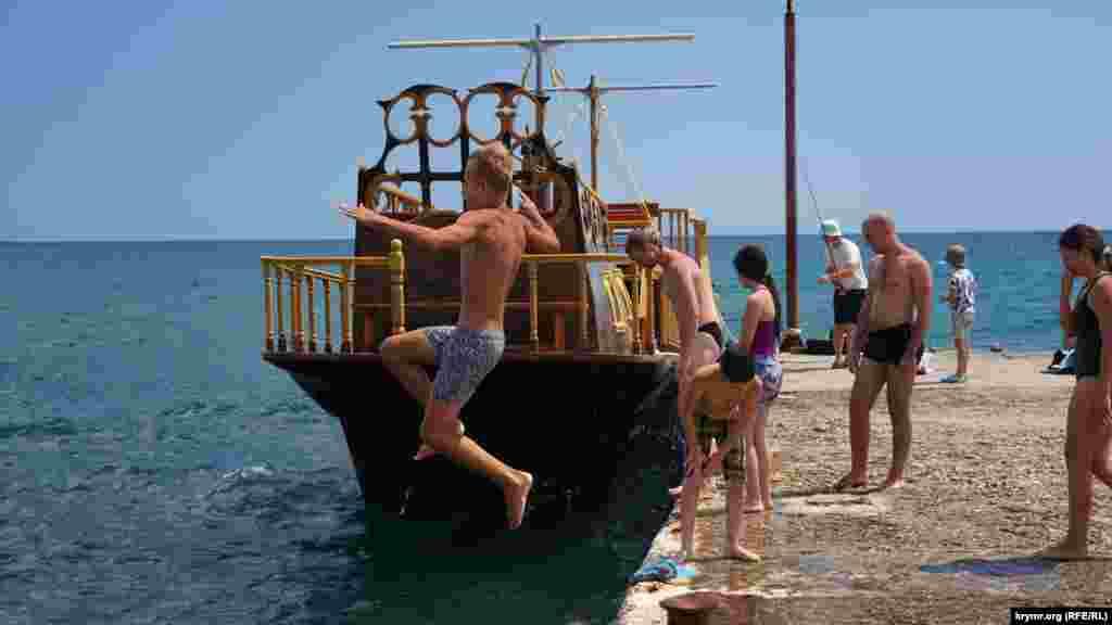 Июнь 2020 года. Крымчанин прыгает с пирса в восточной части поселка Новый Свет, у подножия горы Сокол. Прыгать с пирса или буны в Крыму – запрещено, однако некоторые отдыхающие игнорируют запреты