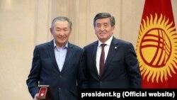 Акын Жолоочу Рысбаев президенттин колунан сыйлык алган учурунда.
