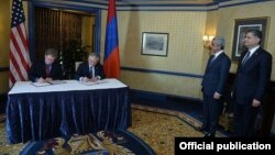 U.S. Assistant Trade Representative Daniel Mullaney (left) and Armenian Foreign Minister Edward Nalbandian sign a U.S.-Armenian Trade and Investment Framework Agreement in Washington on May 7. Armenian President (second right) was present for the signing.