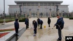 Рабочие моют дорогу у Дворца независимости в Минске накануне встречи президентов Беларуси, Казахстана и России. 24 октября 2013 года.