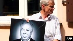 Човек држи постер на Михаил Голованов
