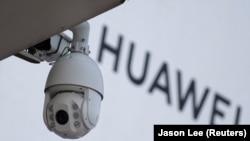 تصویر از یک دوربین مداربسته در کنار نشان شرکت هواوی در نزدیکی مرکز خرید در پکن (عکس از آرشیو)