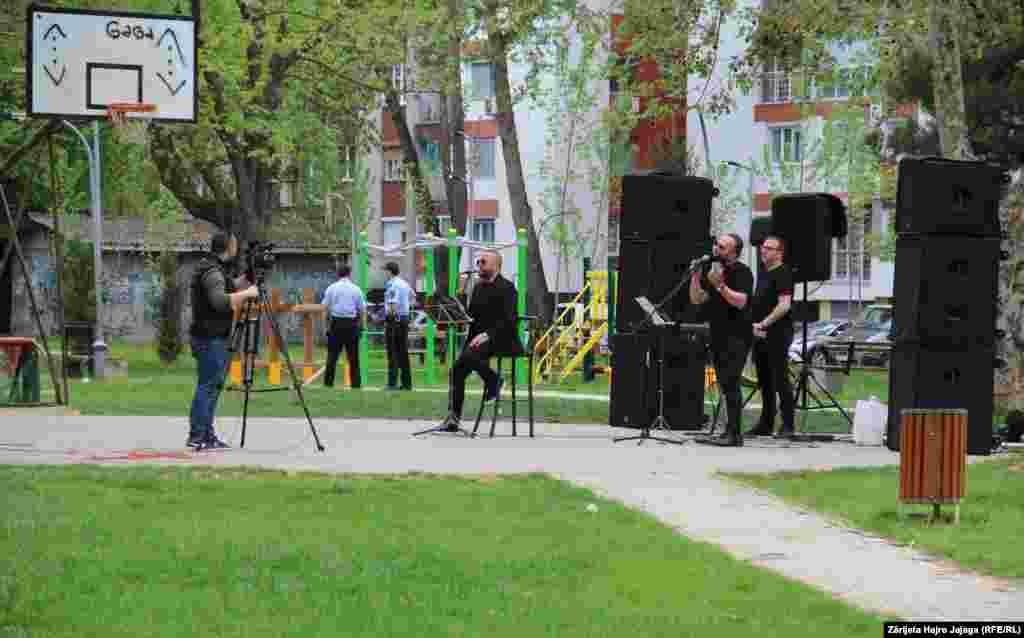 Dy policë qëndrojnë afër vendit ku janë të vendosur grupi muzikor.