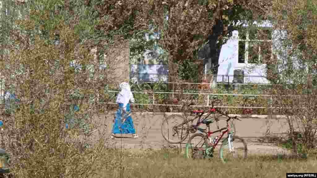 Фердауси атындағы жалпы орта мектебінің ауласында жүрген оқушы қыз.