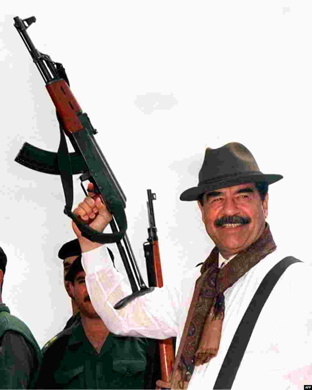 Saddam Hussein in the mid-1990s, posing with an AK-47. After the Iran-Iraq War, his attention turned to oil-rich Kuwait, which he invaded in August 1990.