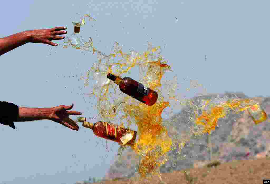 Frontier Corps personnel break liquor bottles in a ceremony in the Shahkas area of the Jamrud Khyber Agency, one of the Federally Administered Tribal Areas of Pakistan. Officials destroyed the contraband as part of International Antidrug Day. (AFP/A Majeed)