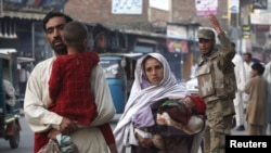 A family walks past a soldier on a street in Mingora, in Swat, on May 20.