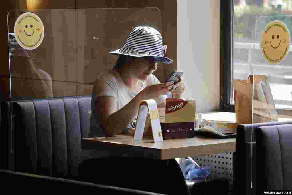 A woman sits behind plastic screening in a newly reopened McDonald's restaurant in Moscow on June 23.