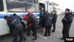 Police detain alleged illegal migrants during a raid at Moscow's Sadovod market on November 19.