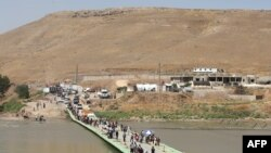 Iraq -- Displaced Iraqis from the Yezidi community cross the Iraqi-Syrian border along the Fishkhabur bridge over the Tigris River at the Fishkhabur crossing, in northern Iraq, August 11, 2014