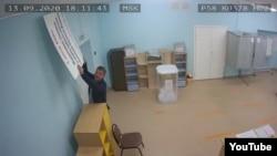 Сотрудник УИК №378 в селе Бессоновка Пензенской области пытается закрыть камеру наблюдения плакатом, призывающим голосовать за поправки к Конституции, 13 сентября 2020 года