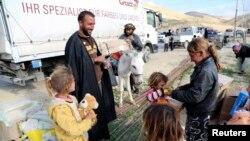 Дети из числа езидов, вынужденно покинувших свои дома, получают гуманитарную помощь. Синджар, 22 декабря 2014 года.