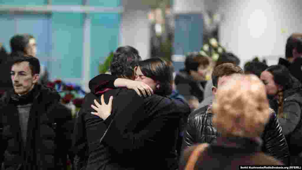 Mourners embrace at the airport.