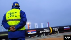 A construction worker stands in front of two giant pipes arranged to be welded together near the village of Sajkas, 80 kilometres north of Serbian capital Belgrade, November 24, 2013