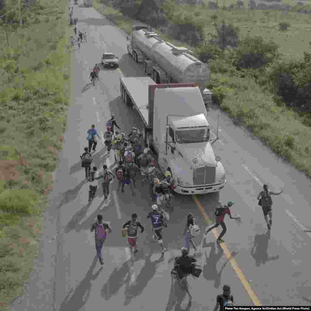 Мигранты бегут загрузовиком, водитель которого готов их подвезти. Окрестности Тапанатепека (Мексика), 30октября 2018года. World Press Photo, номинация «Фоторепортаж года», победитель— Питер Тен Хупен, Agence Vu/Civilian Act