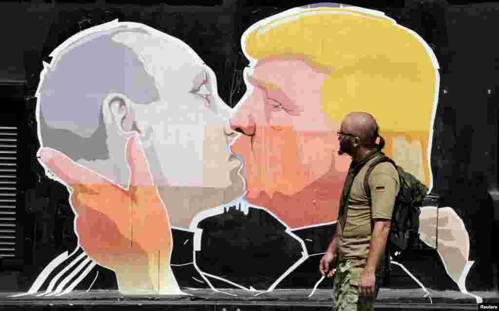 Një njeri duke kaluar pranë grafiteve paragjykuese ndaj kandidatit republikan, Donald Trump me presidentin rus, Vladimir Putin, në Vilnius.