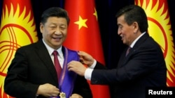 Kyrgyz President Sooronbai Jeenbekov (right) awards Chinese President Xi Jinping with the Manas Order at a meeting in Bishkek in June 2019.