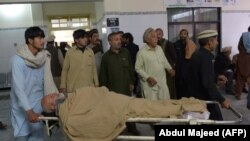 Pakistani men transport an injured bombing victim at a hospital in Kohat on November 23.