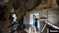 Russia -- A local resident looks at the debris of a house damaged by floods in the town of Krymsk in Krasnodar region, 08Jul2012