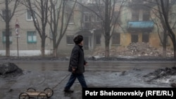 A man pulls a wagon past a destroyed building in Debaltseve.