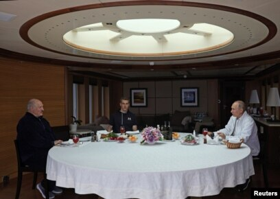 Lukashenka (left) and his son Mikalay (center) dine at sea with Putin aboard the Chaika.