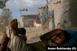 A boy wakes from an afternoon snooze in a village near Bukhara in 2013.