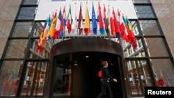 A woman walks past the entrance of the European Council headquarters in Brussels. (file photo)