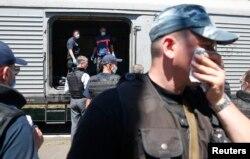 Тела погибших пассажиров рейса МН17 грузят в вагоны в городе Торез