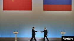 Президент Китая Си Цзиньпин (слева) и президент России Владимир Путин идут навстречу друг другу. Москва, 22 марта 2013 года.