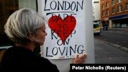 Женщина крепит плакат возле моста в память о погибших в теракте. Лондон, 4 июня 2017 года.