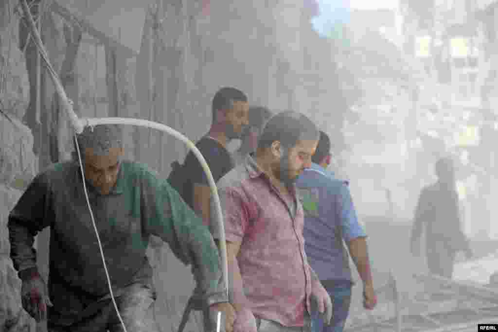 On October 11, dust-covered civilians inspect the rubble of a destroyed building in the Bustan al-Qasr district of Aleppo. Backed by Russian air strikes, Syrian government forces have advanced into rebel-held areas in a bid to recapture the entire city.
