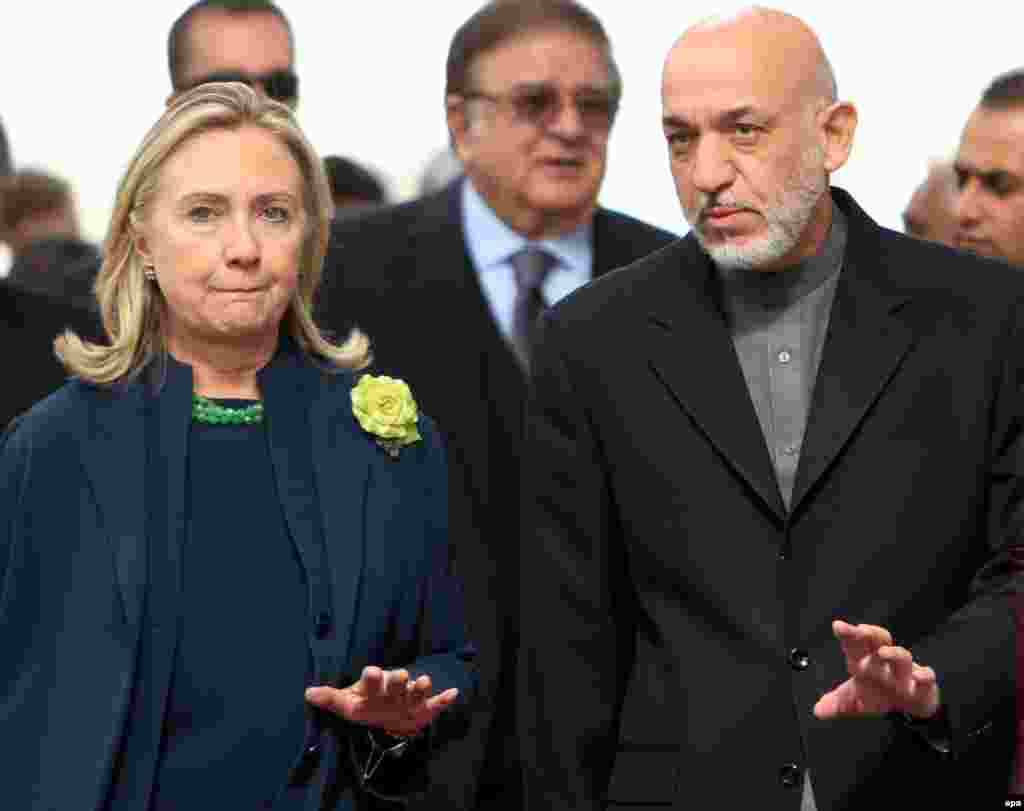 Karzai accompanies U.S. Secretary of State Hillary Rodham Clinton as they arrive for a joint press conference in Kabul on October 20, 2011.