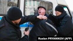 Полиция ходимлари митинг иштирокчиларидан бирини қўлга олиб, полиция бўлимига олиб кетиш учун машинага ўтиришга мажбурламоқда. Олмаота, 2020, 1 март.